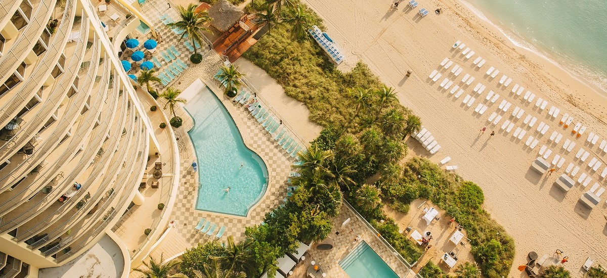 aerial view of hotel pools and tropical beach