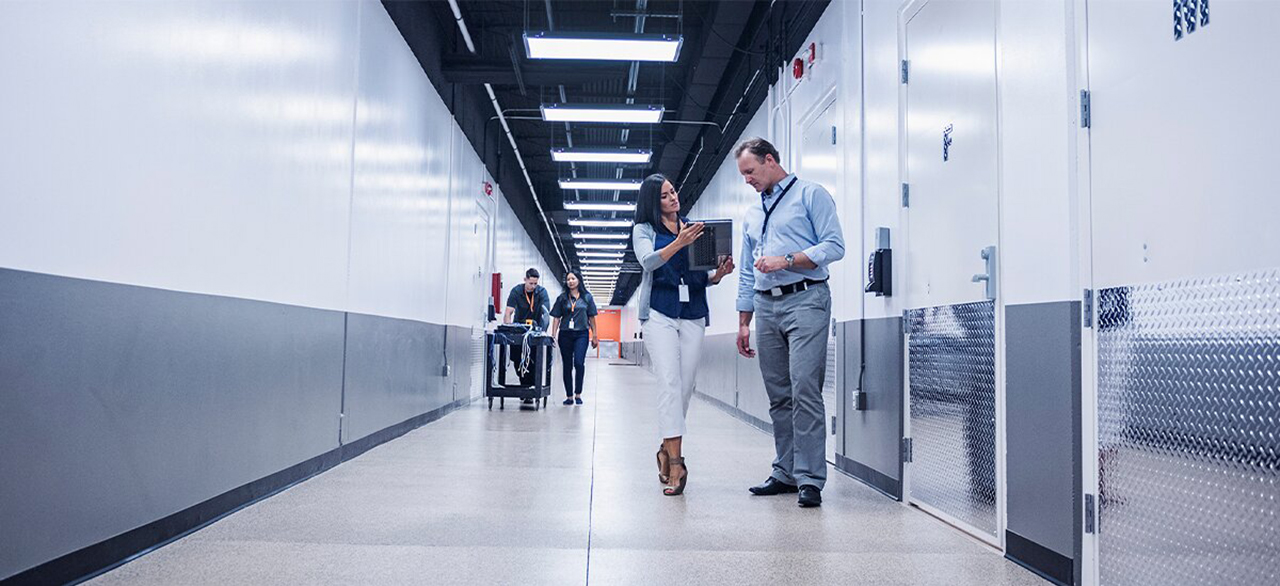 woman and man talking in a corridor of a data center